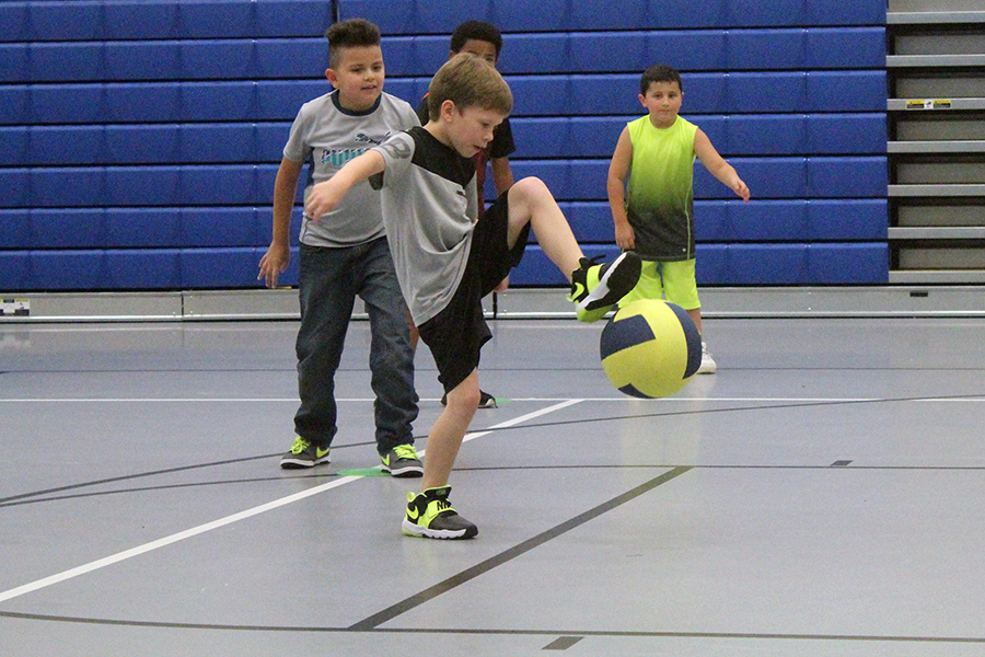A boy kicks a ball in gym class