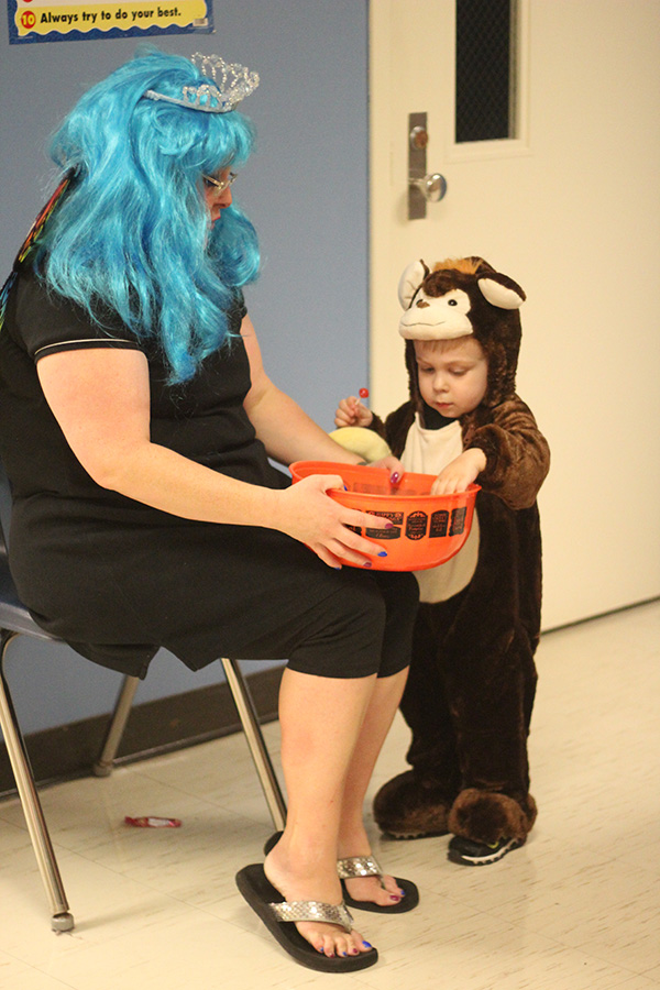 A boy dressed as monkey takes candy out of a bowl.