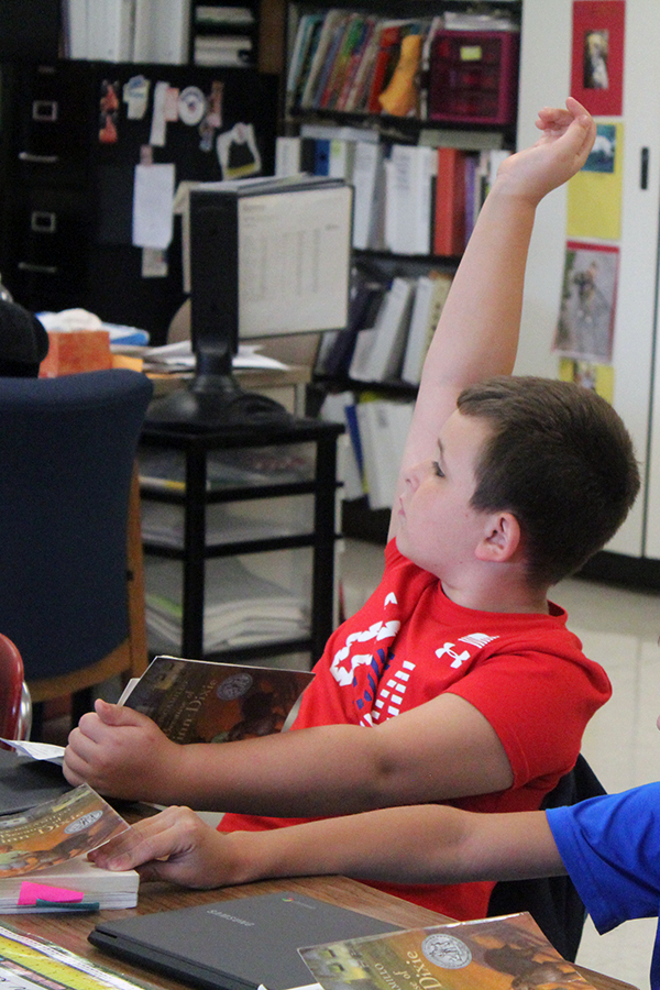 A student raises his hand to ask a question about the book