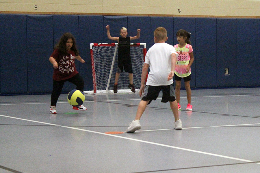 The girl kicks the ball away from the other students