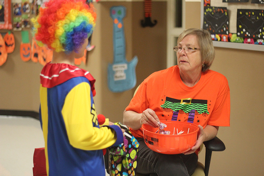 A student dressed as a clown Trick or Treats.