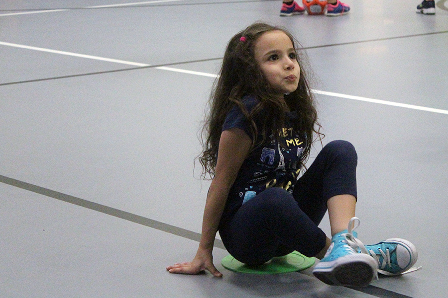 A student sits down as she waits for instructions for the game