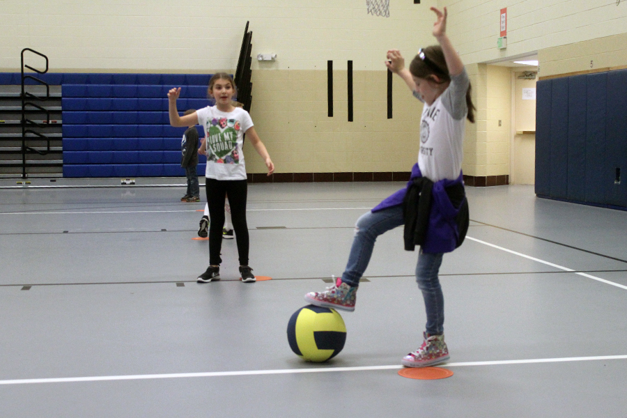 The girl gets ready to kick the ball to one of her teammates