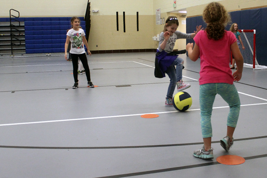 The girl gets ready to kick the ball and try to score a point