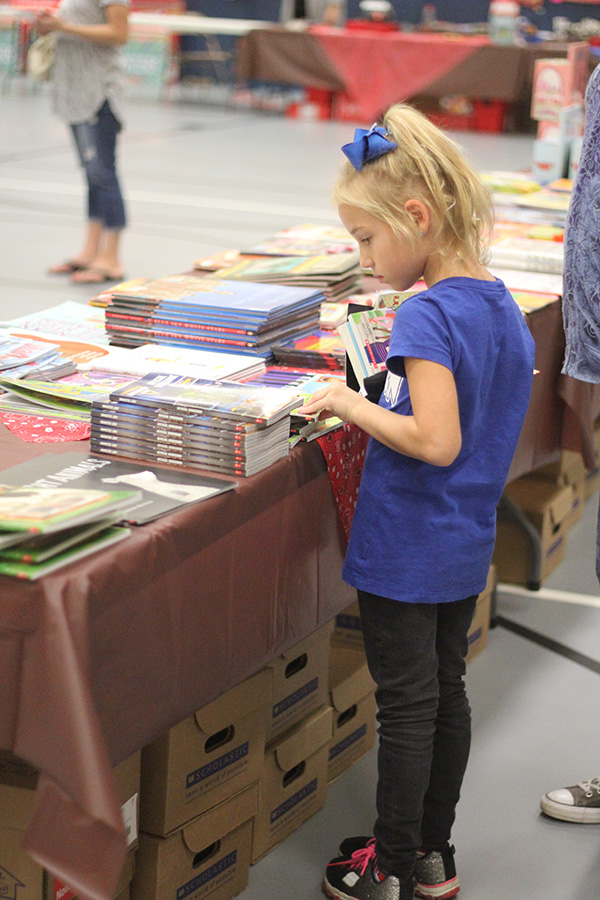 A girl looks at the table of books.