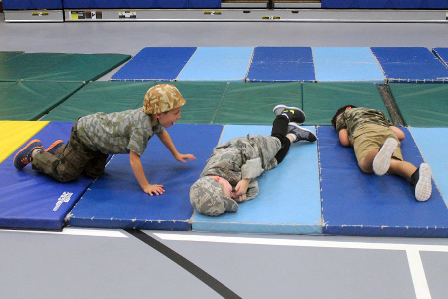 Three students roll on a mat after answering a math question