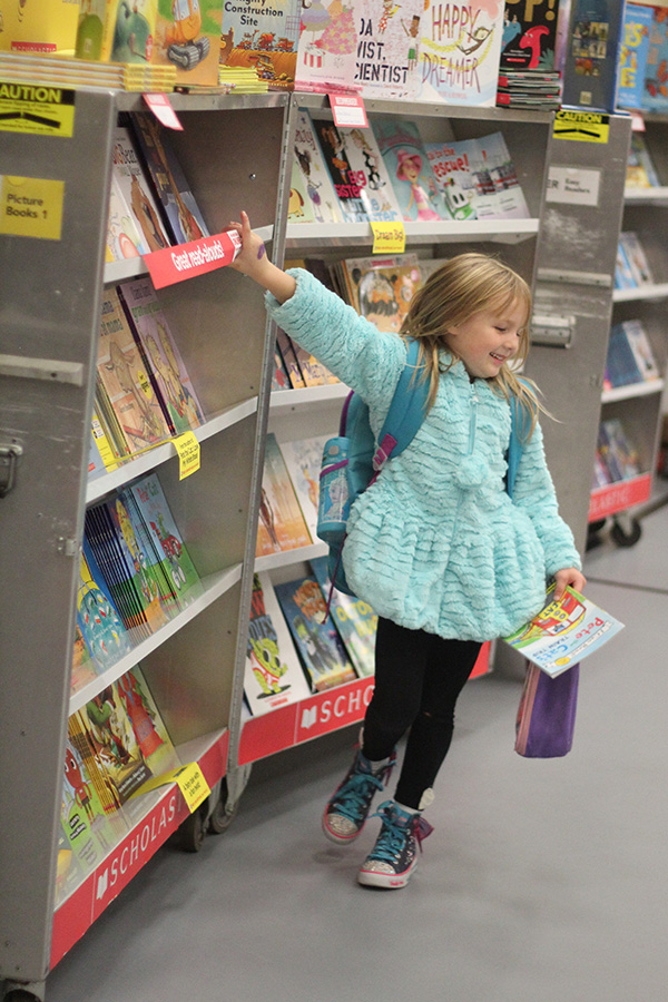 A girl shops around and looks for books to buy.