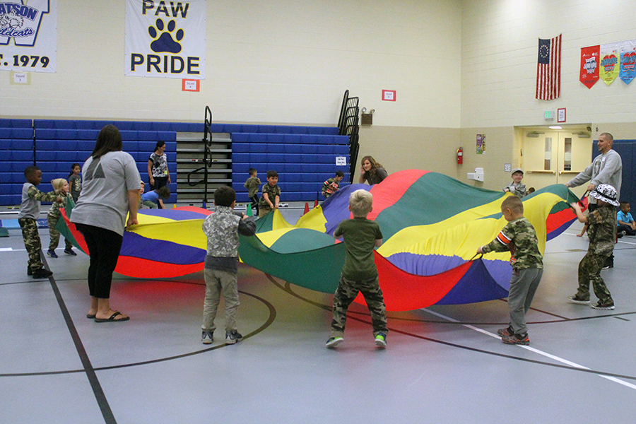 A group of kindergartner's wave a parachute around