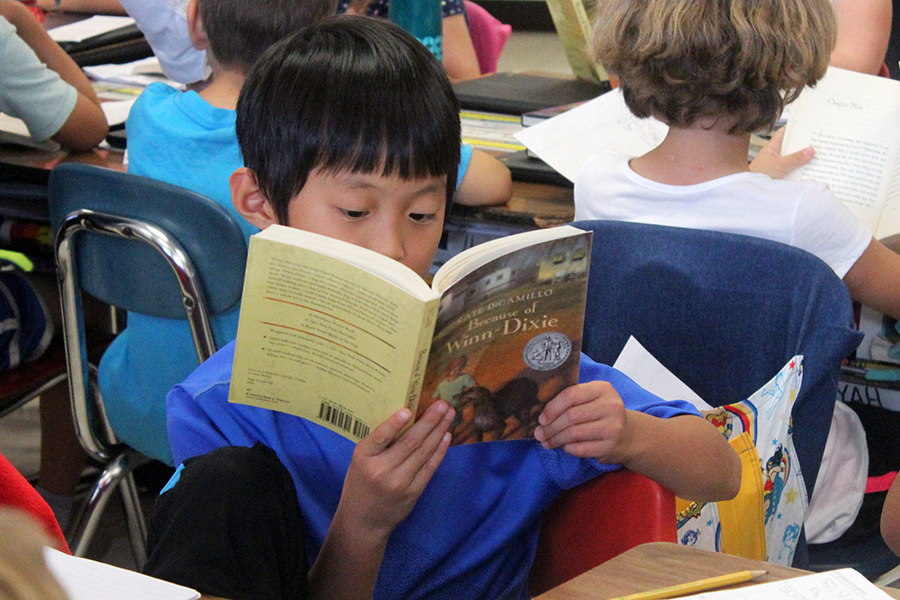 A boy pays attention to the book that Mrs. Crary reads out loud