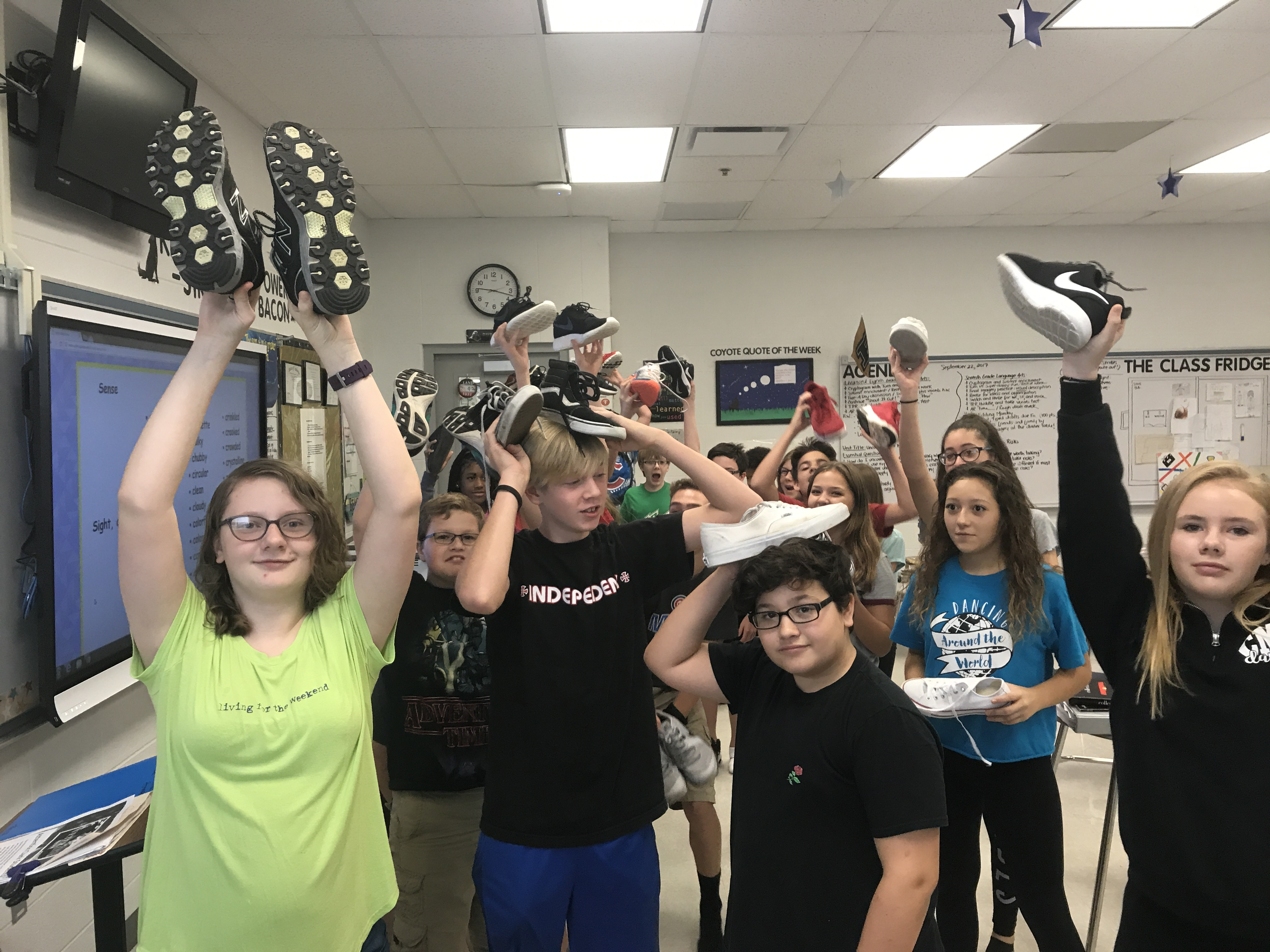 students holding up shoes