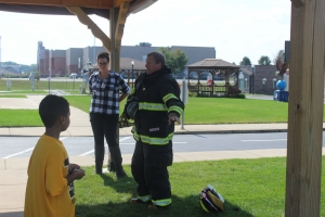 Protsman students sit and listen to a firefighter.