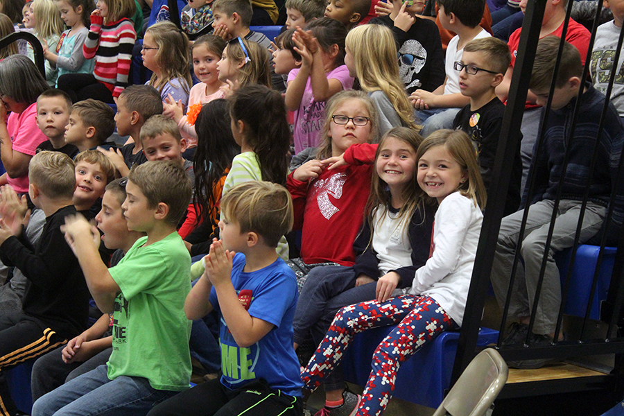 Girls smile at the camera at the assembly.