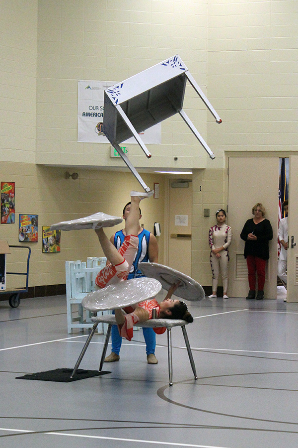 A Chineese acrobat flips a table with her feet.