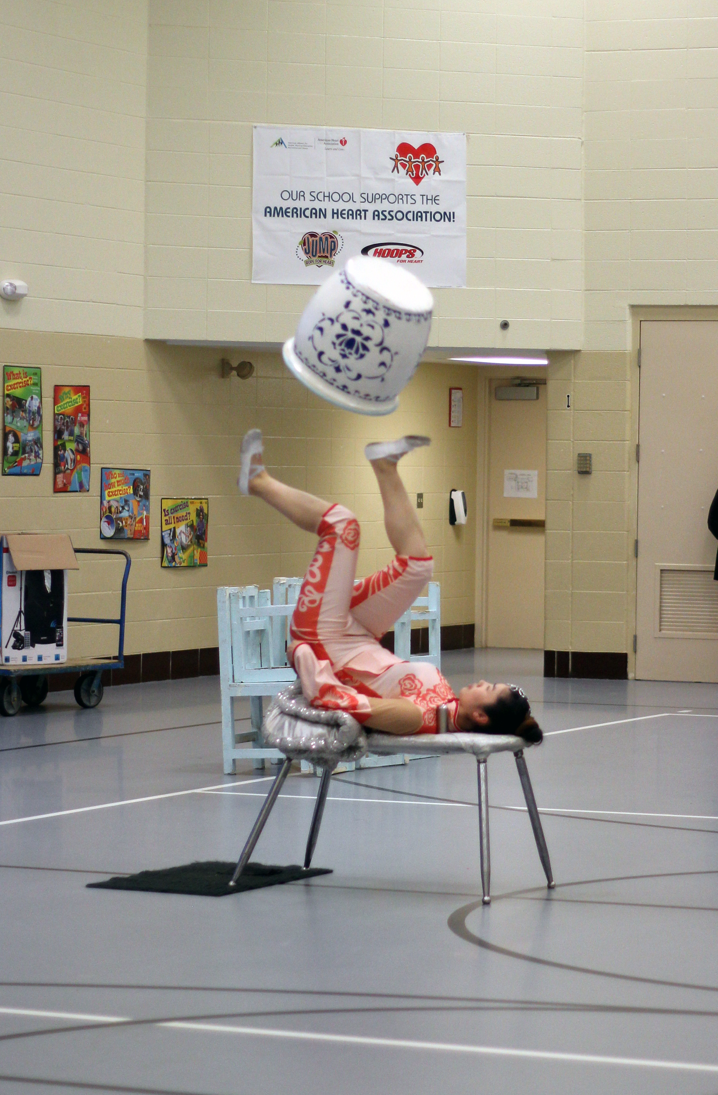 The acrobat flips the pot with her feet.