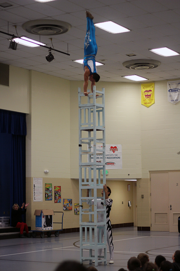 The Chinese acrobat stands on top of a stack of chairs.