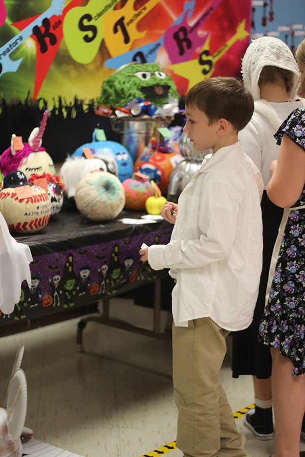 A boys looks at all the decorated pumpkins.