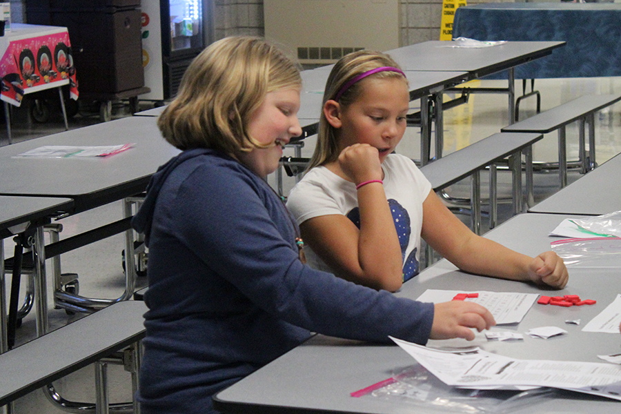Two girls work together to figure out a math game