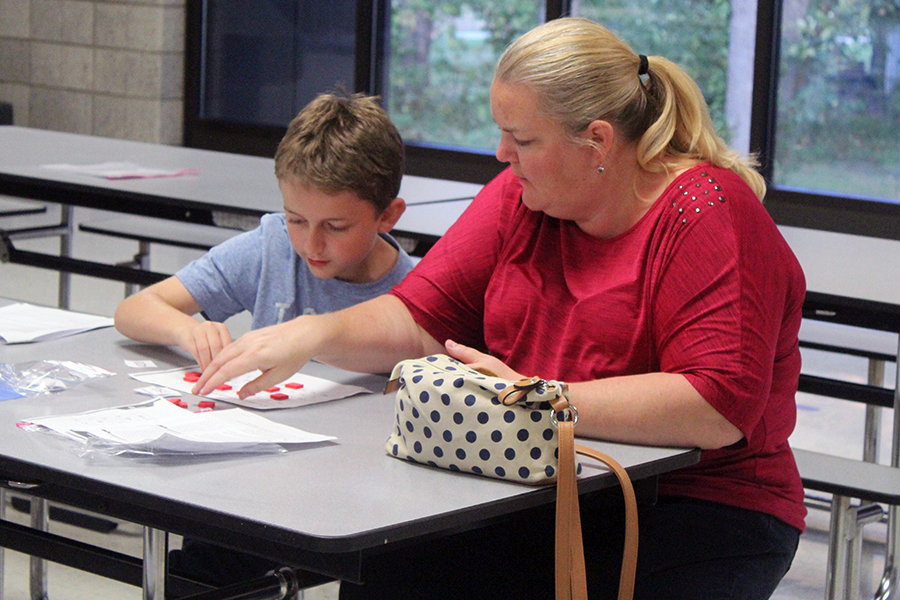 A mother and her son sit down to complete a math game about the new curriculum