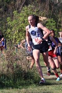 Girls Varsity cross country runner turns the corner towards the finish line.