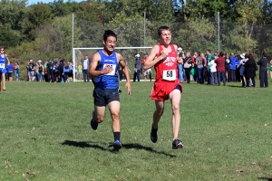 Boys cross contry runner races towards the finish line at full speed.
