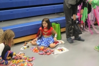 Two girls sit and count the candy they have recieved