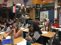 Students listen to their teacher as he teaches them a new assignment.