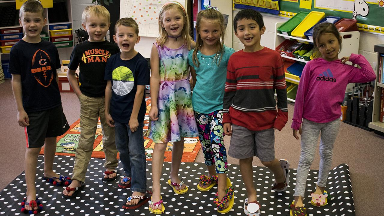 Mrs. Bussey's class models their flip flops.