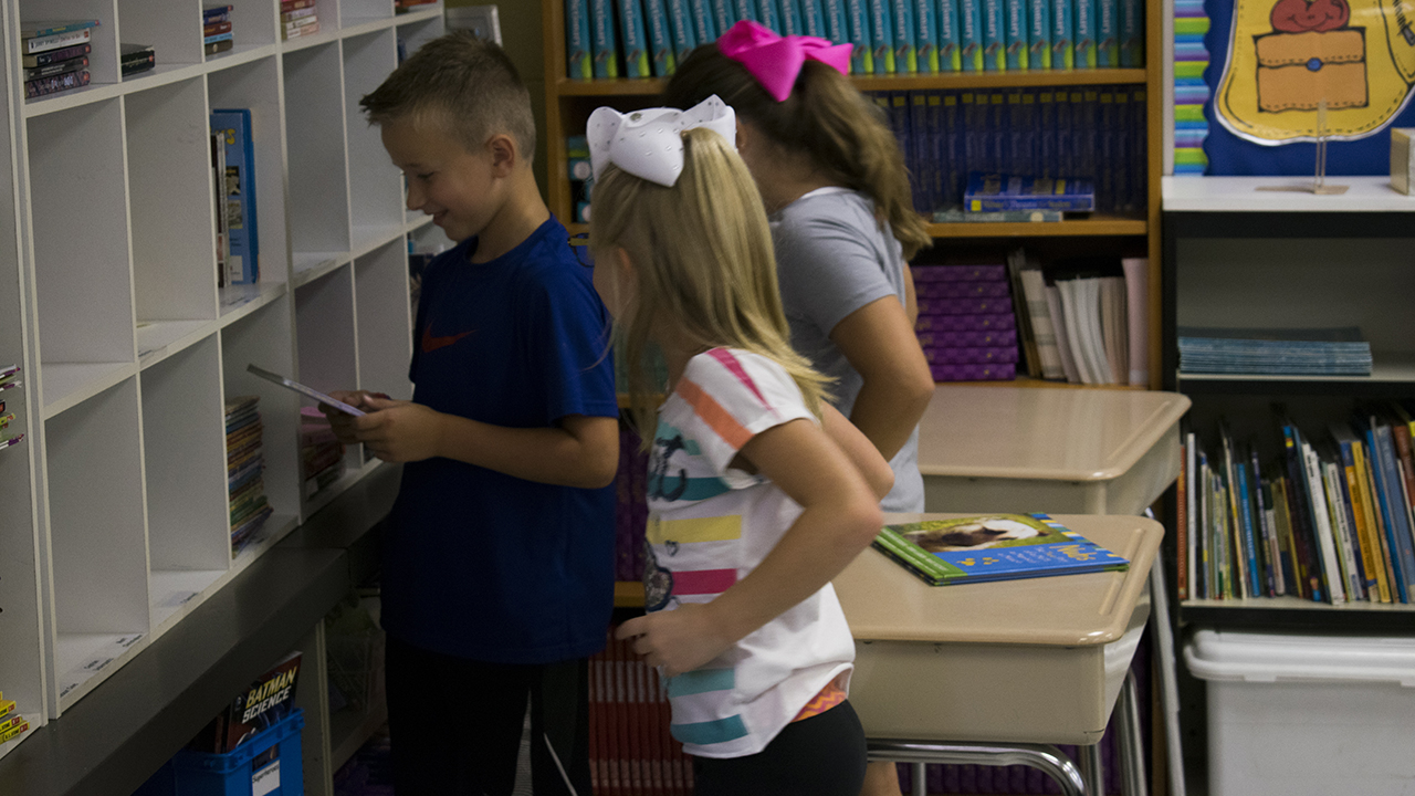 Students organize books on the bookshelf in Mrs. Pawlak's class.