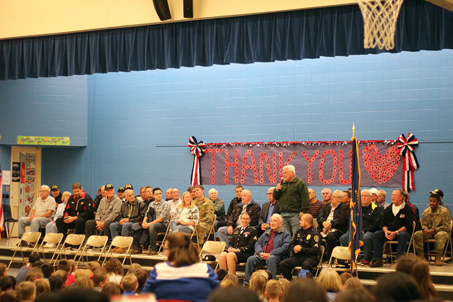Veterans sit upon the stage.