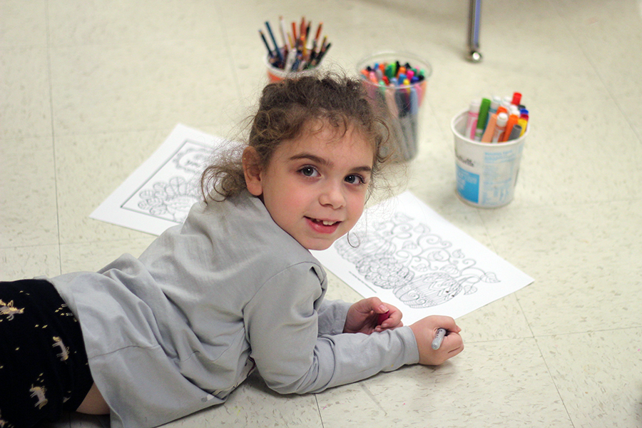 A girl smiles while in art class.