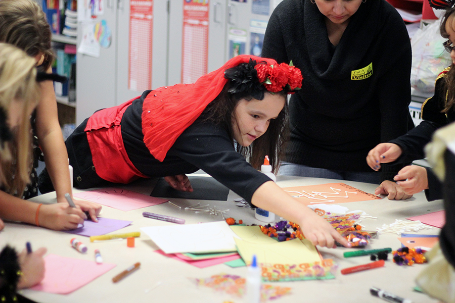 Students make Halloween crafts.