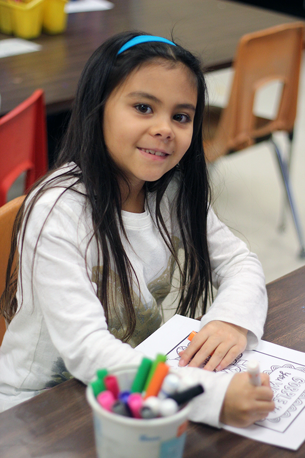 A girl smiles while working on her project.