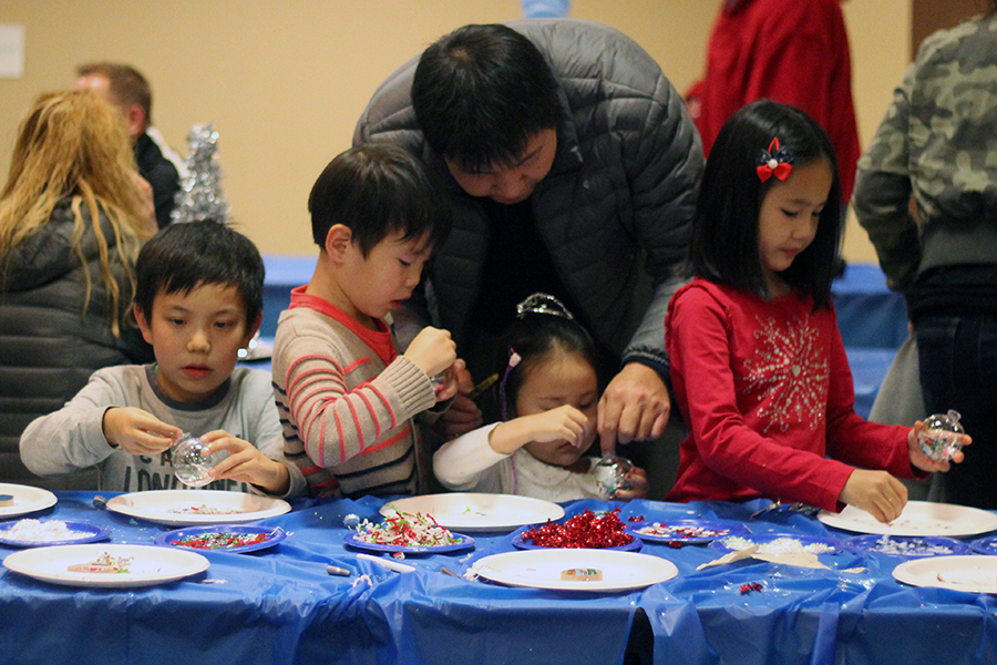 Kids paint ornaments at a craft station