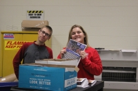 students pose with the pamphlets they made.