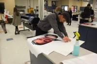 A senior student cuts a poster he made.