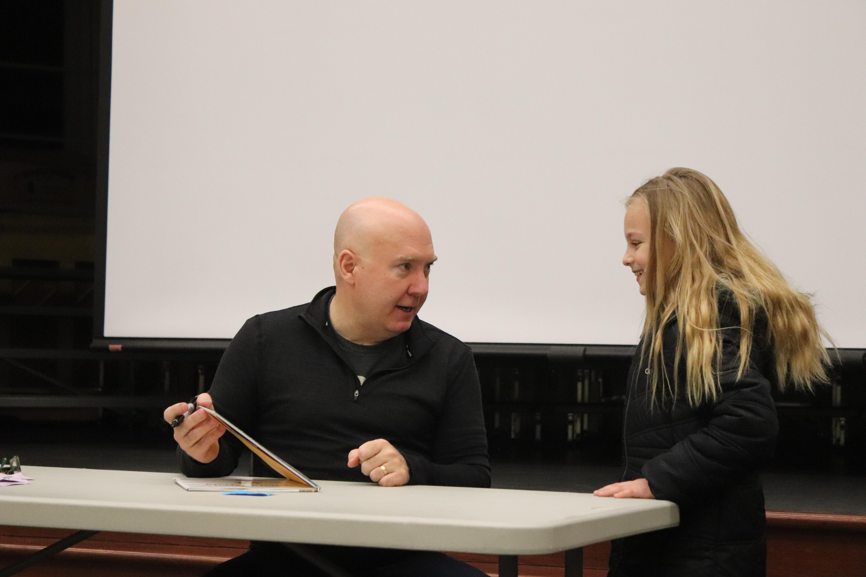 Reynolds makes a girl laguh at his book signing.