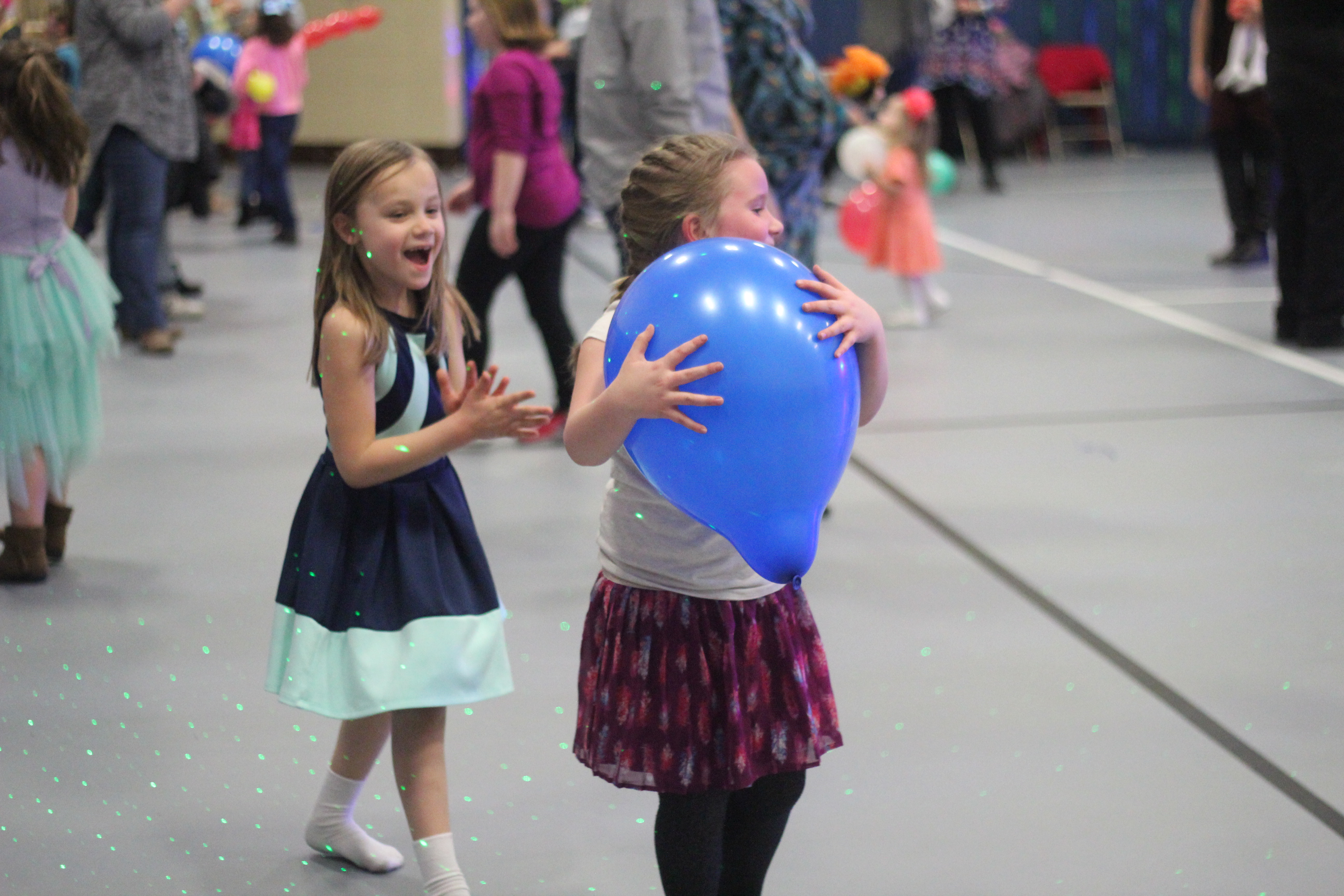 Two girls play with a balloon at the dance.