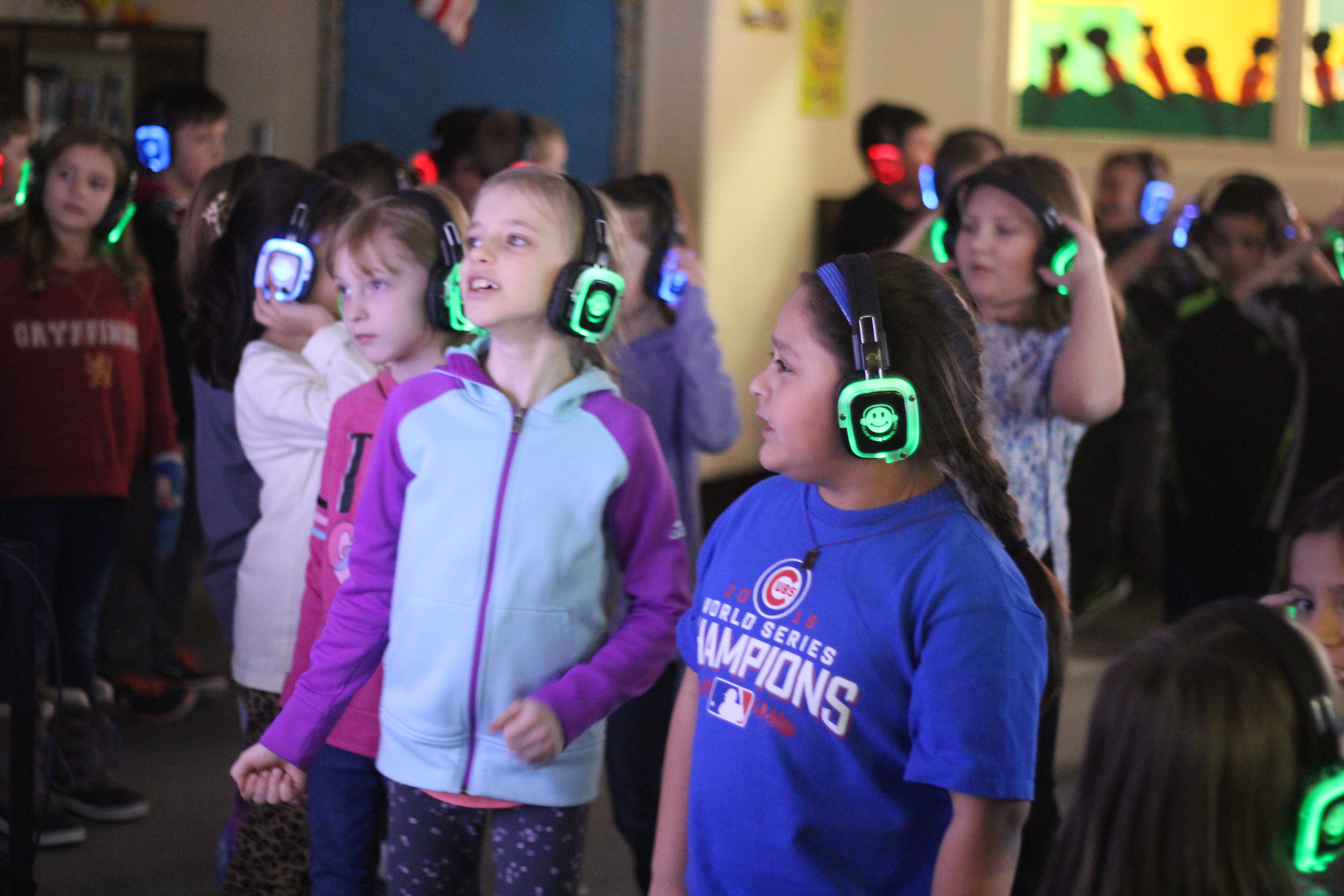 Students watch music videos and listen to them with headsets.