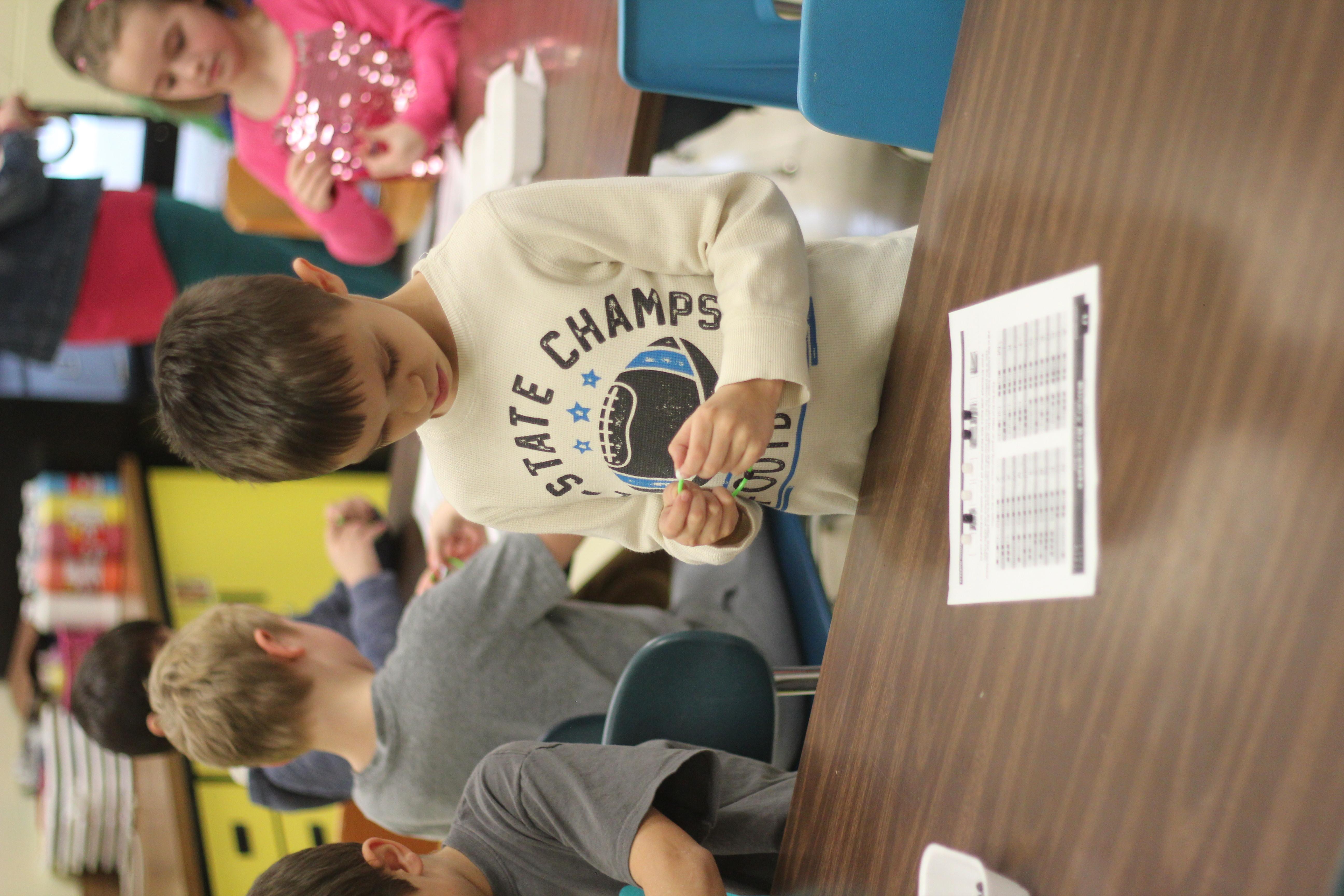 Students make coding braclets.
