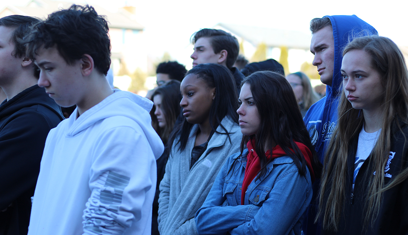 Students stand and listen to student speaker