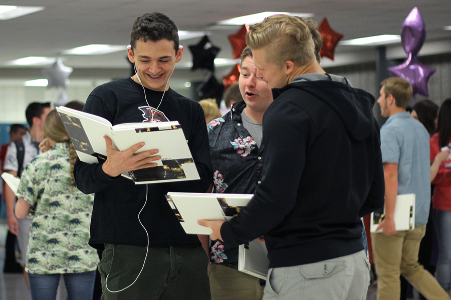 students smile while looking through the 2017 yearbook.
