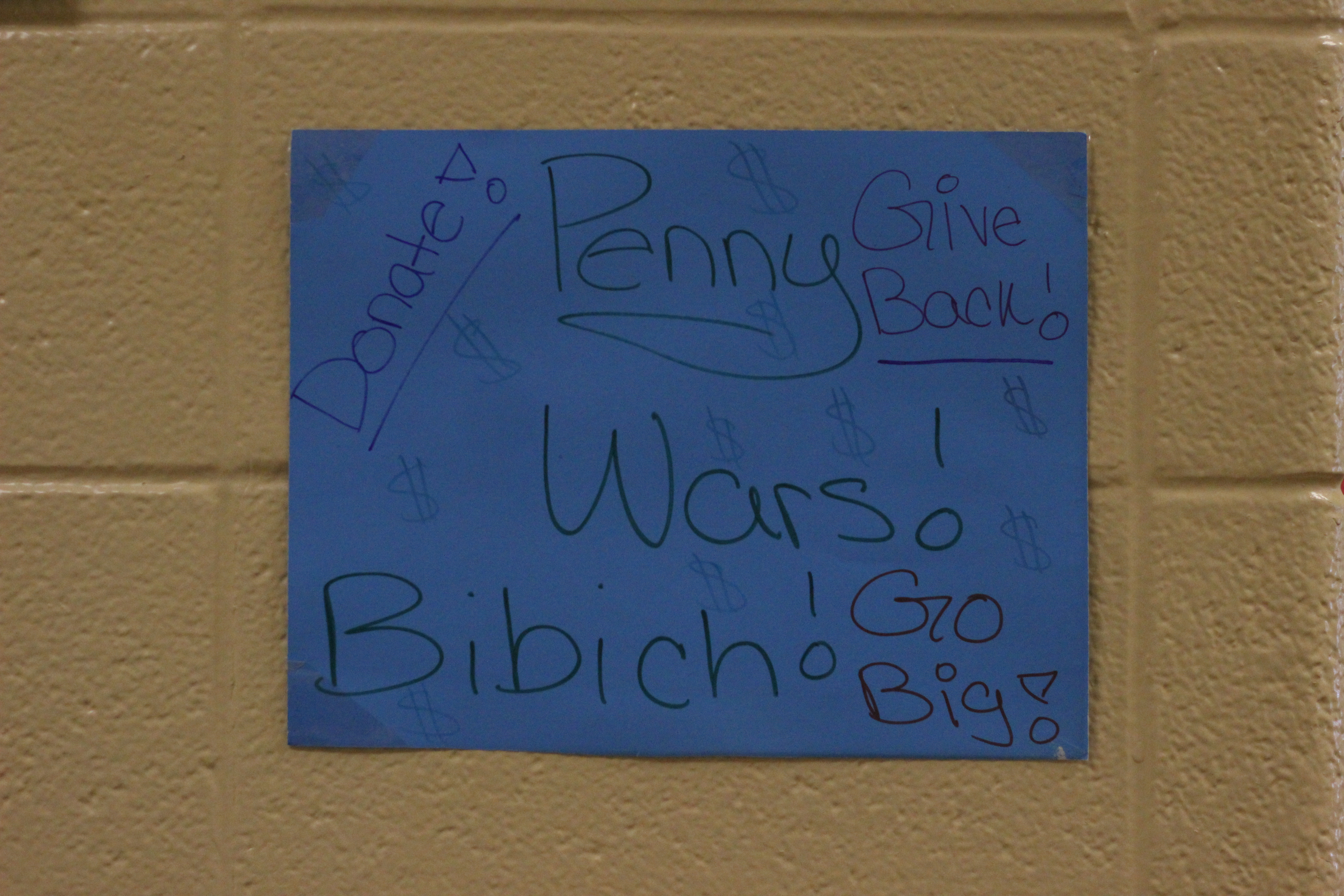 A student made poster for the penny wars hangs in the hallway