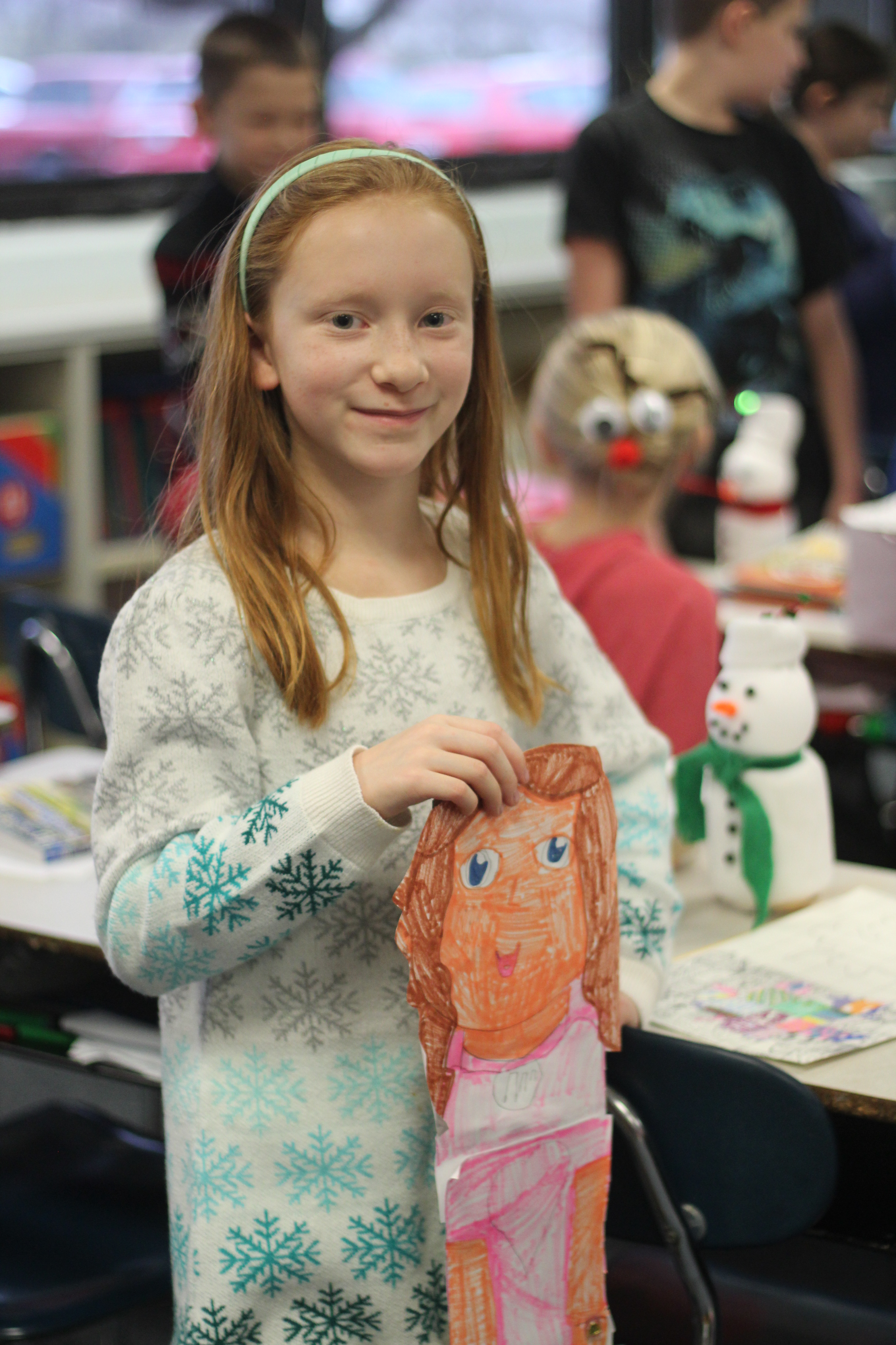 A girl smiles at the camera with her project
