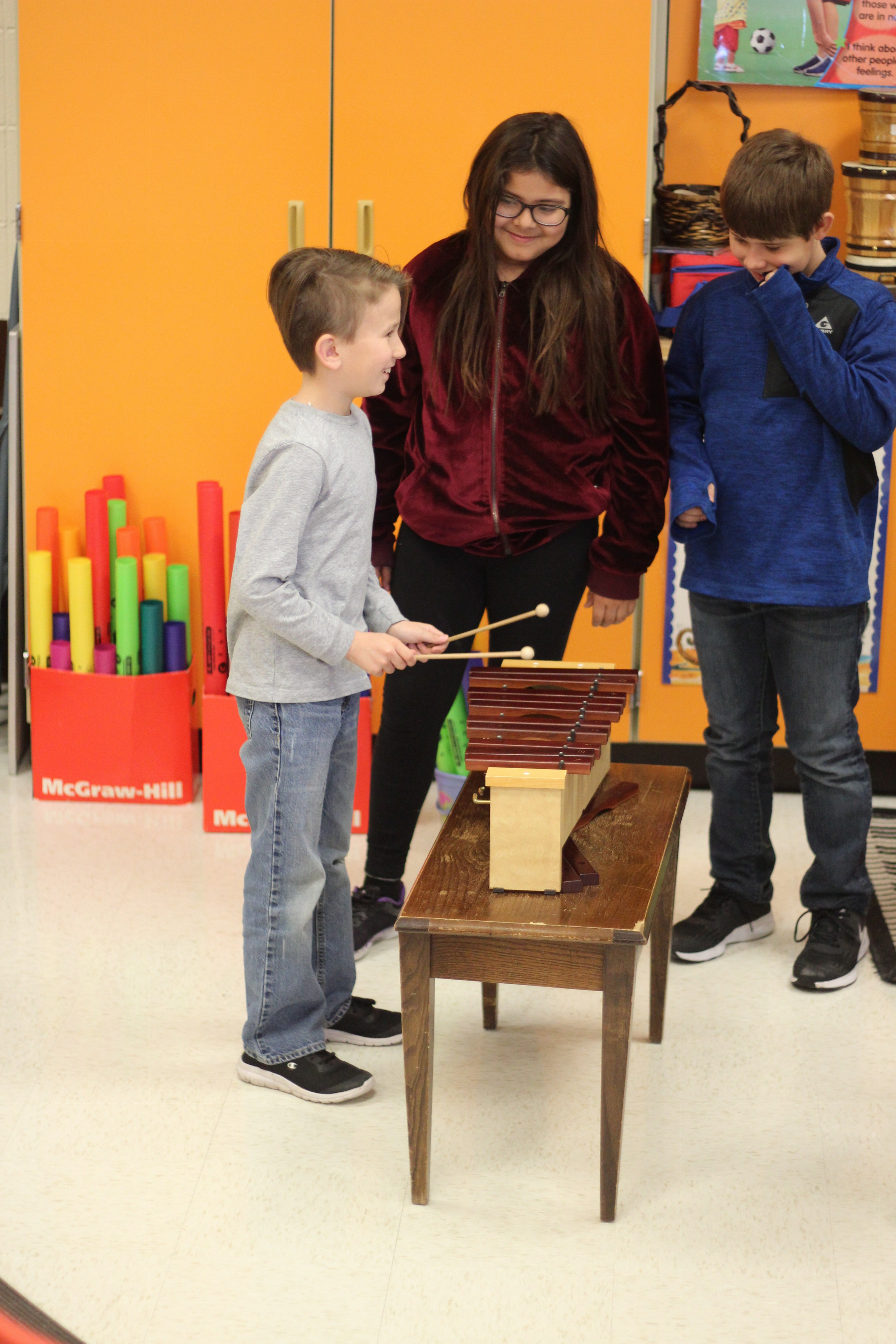 Students play the xylophone.