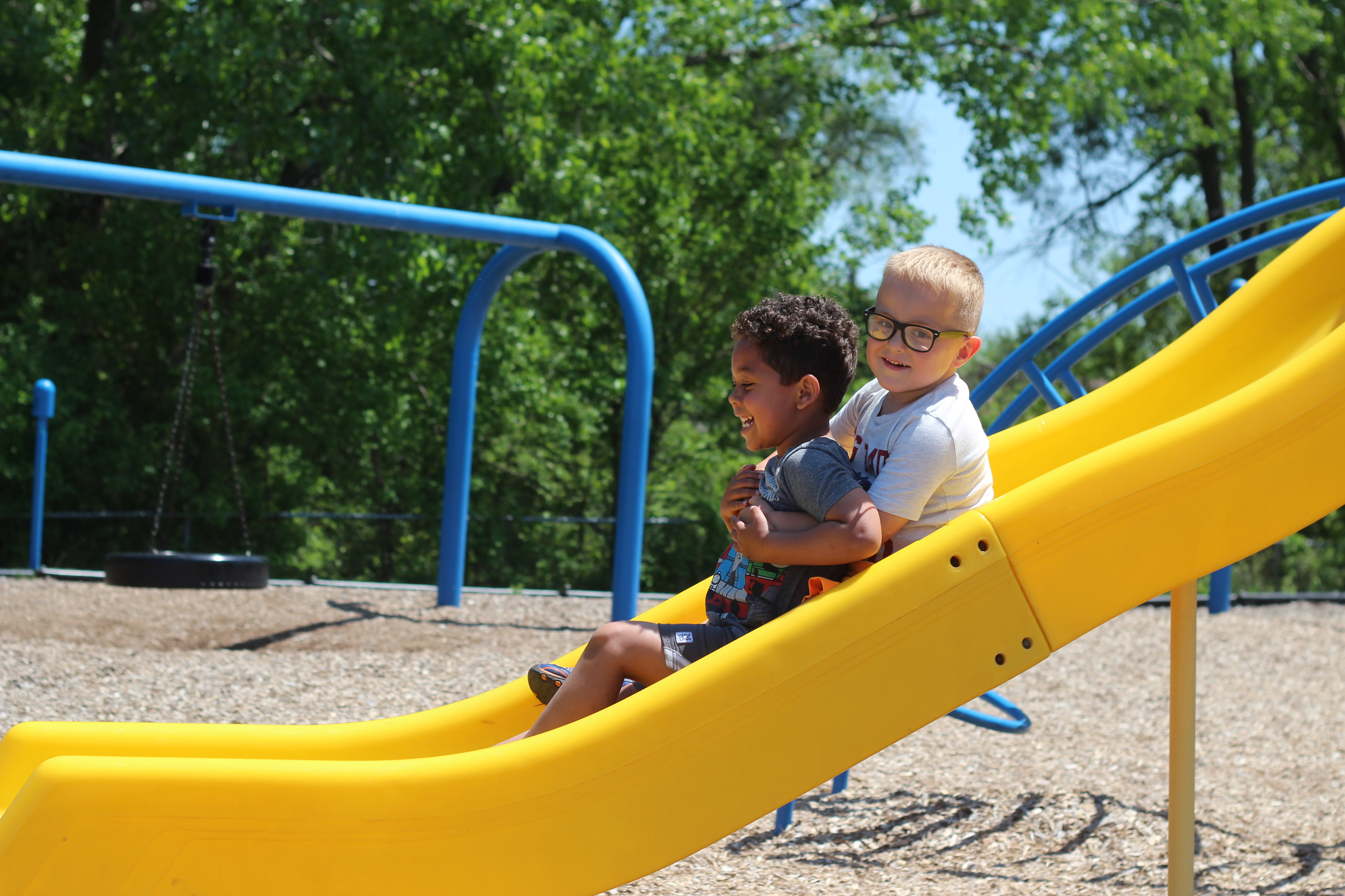 Two boys go down the slide