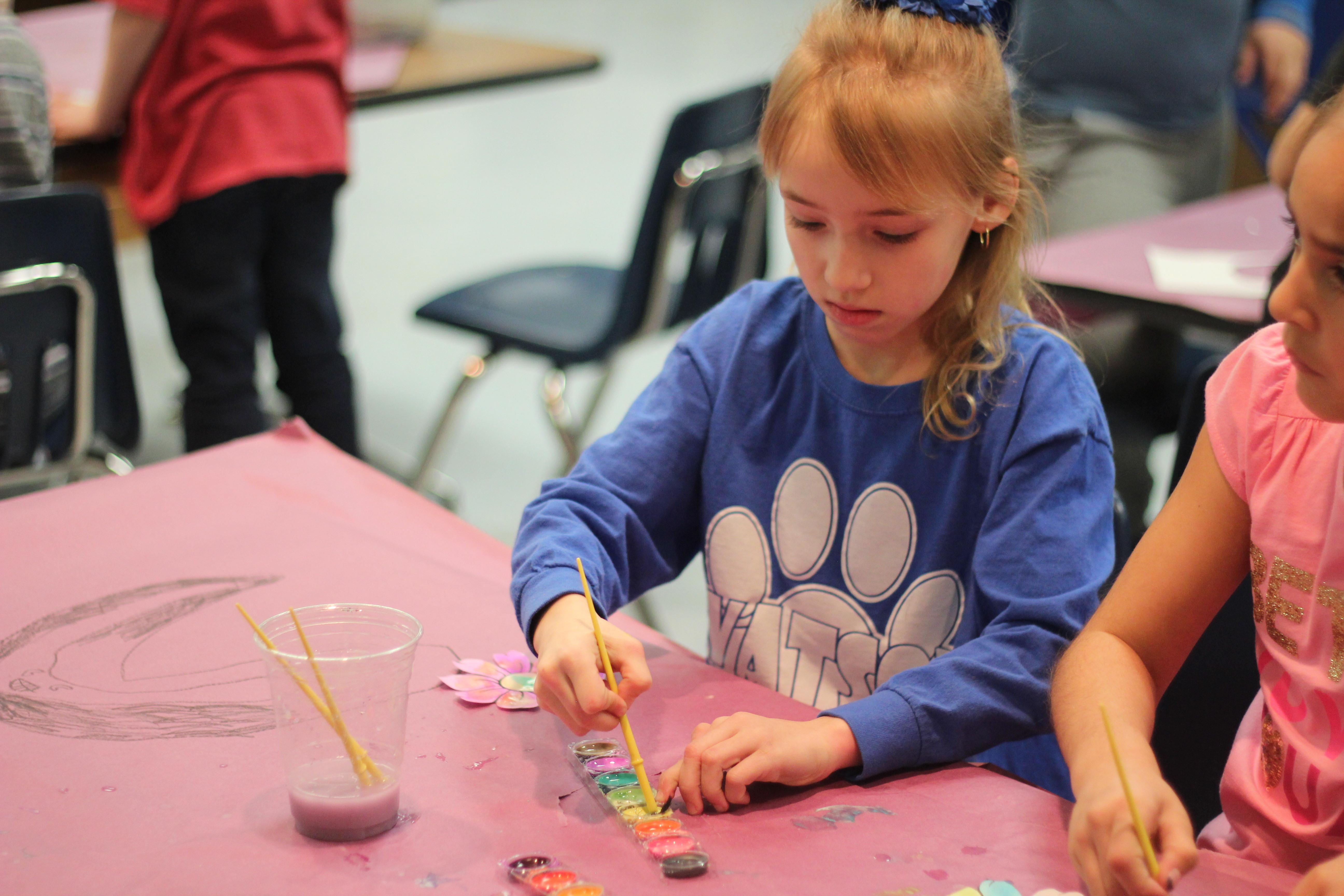 A student paints flowers.