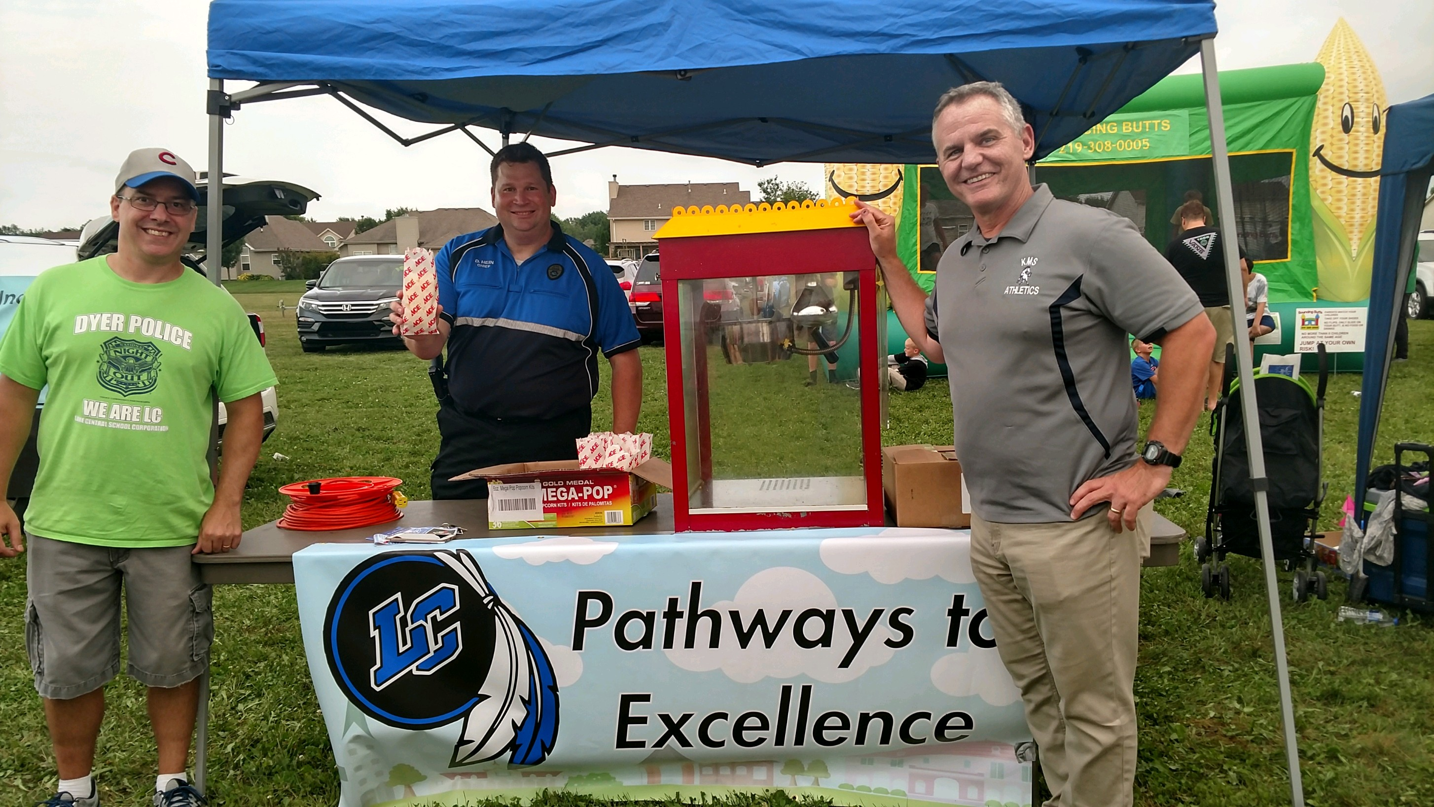 Kahler Principal Ken Newton, Dyer Police Chief (LC Graduate) David Hein, and Asst Principal Tim Doyle prepare to pop corn at the National Night Out in Central Park on Tuesday August 7th.