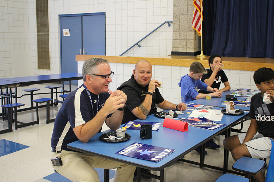 School officials smile while eating breakfast
