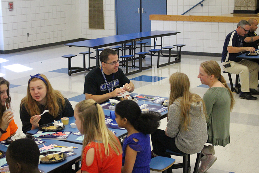 Mr. Newton eats breakfast with students.