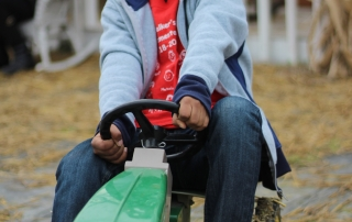 Student rides on a toy tractor